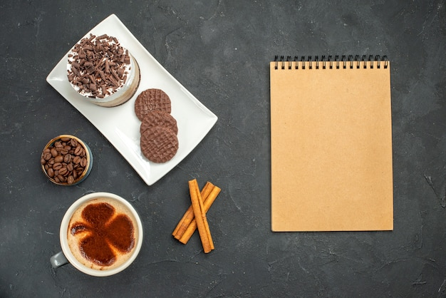 Top view chocolate cake and biscuits on white rectangular plate cup of coffee cinnamon sticks bowl with coffee seeds a notebook on dark isolated background
