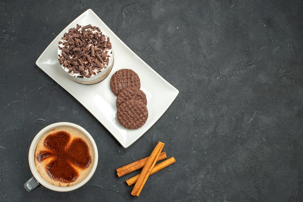 Top view chocolate cake and biscuits on white rectangular plate cup of coffee cinnamon sticks on dark isolated background