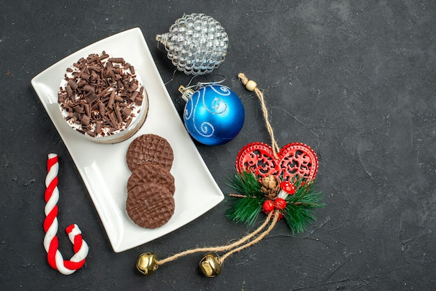 Vista dall'alto torta al cioccolato e biscotti su piatto rettangolare bianco albero di natale giocattoli su sfondo scuro isolato
