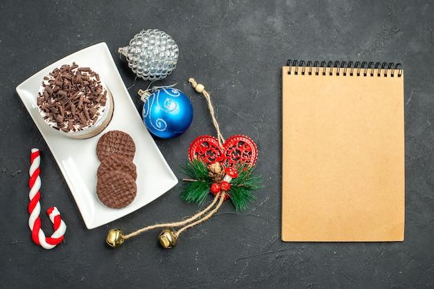 Vista dall'alto torta al cioccolato e biscotti su piatto rettangolare bianco albero di natale giocattoli un blocco note su sfondo scuro isolato