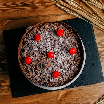 A top view chocolate cake decorated with cherries round delicious inside brown cake