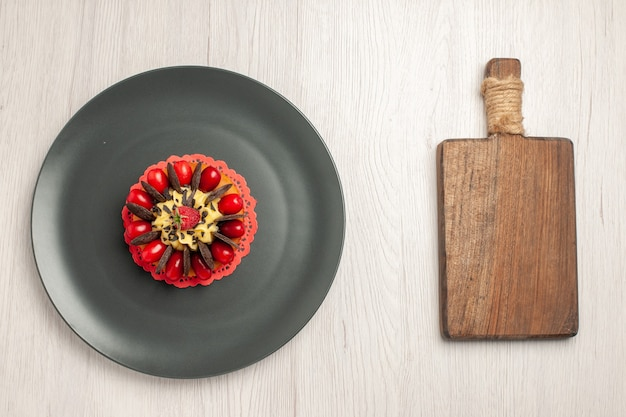 Top view chocolate cake rounded with cornel and raspberry in the center in the grey plate and a chopping board on the white wooden background