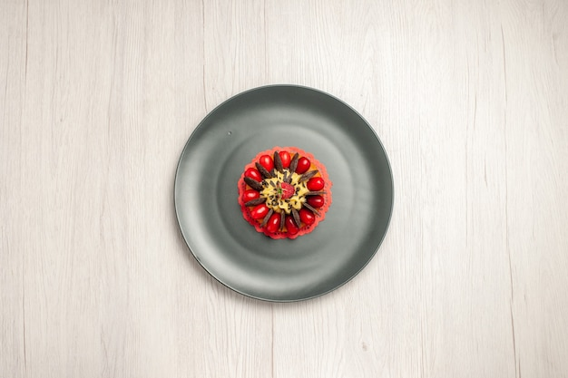 Top view chocolate cake rounded with cornel and raspberry in the center in the grey plate on the white wooden background