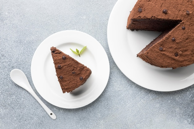 Top view of chocolate cake slice with spoon and mint