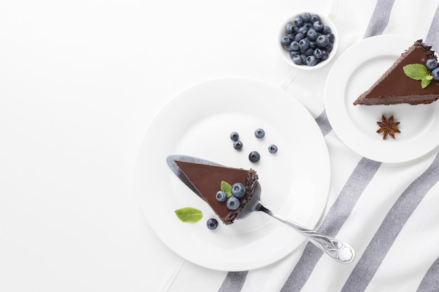 Top view of chocolate cake slices on plates with blueberries