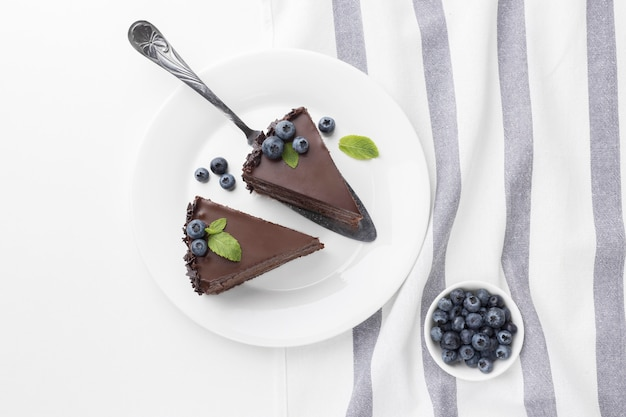 Top view of chocolate cake slices on plates with bowl of blueberries