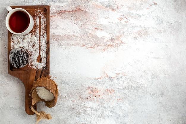 白い机の上にお茶とチョコレートケーキの上面図チョコレートケーキビスケットシュガー甘いクッキー