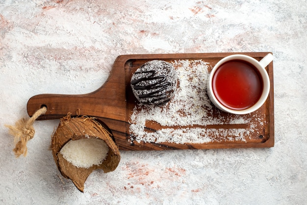 Vista dall'alto torta al cioccolato con una tazza di tè su sfondo bianco chiaro torta al cioccolato biscotto zucchero dolce biscotto
