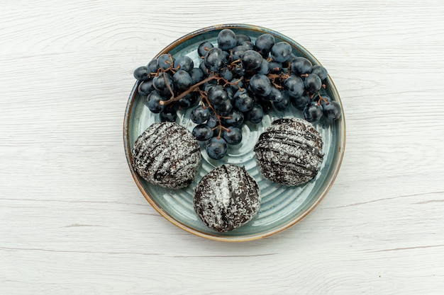 白い背景の上のアイシングと新鮮な黒ブドウでおいしいトップビューチョコレートケーキフルーツケーキチョコレート甘い新鮮な砂糖ビスケット