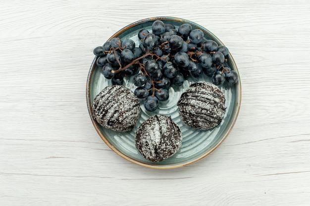 Vista dall'alto torte al cioccolato deliziose con glassa e fresche uve nere su sfondo bianco torta di frutta al cioccolato dolce zucchero fresco biscotto