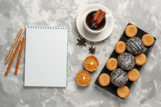 Torte al cioccolato vista dall'alto con biscotti e tazza di tè sulla superficie bianca chiara