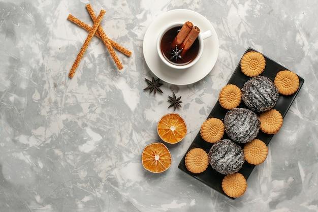 Torte al cioccolato vista dall'alto con biscotti e tazza di tè sulla superficie bianca