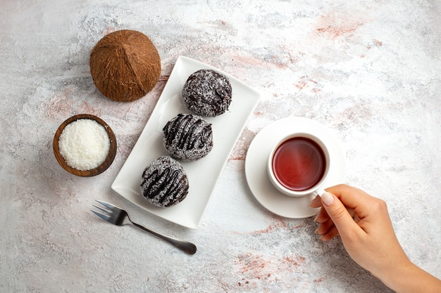 Вид сверху шоколадные торты с чашкой чая и кокосом на белой поверхности шоколадный торт бисквитное сахарное сладкое печенье