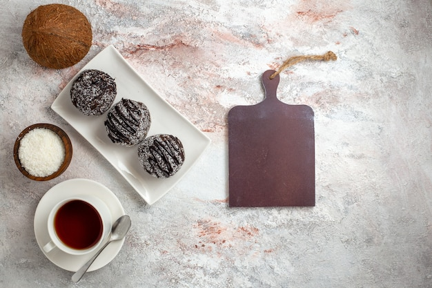 白い背景の上のお茶とチョコレートケーキの上面図チョコレートケーキビスケットシュガー甘いクッキー