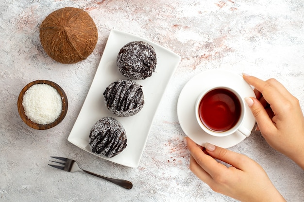 Top view chocolate cakes with cup of tea and coconut on the white surface chocolate cake biscuit sugar sweet cookie