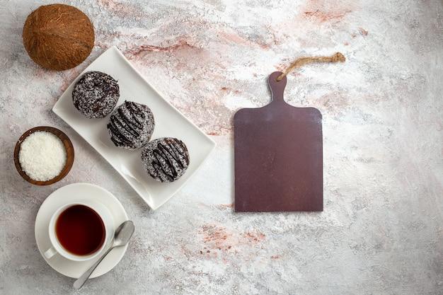 Vista dall'alto torte al cioccolato con una tazza di tè su sfondo bianco torta al cioccolato biscotto zucchero dolce biscotto