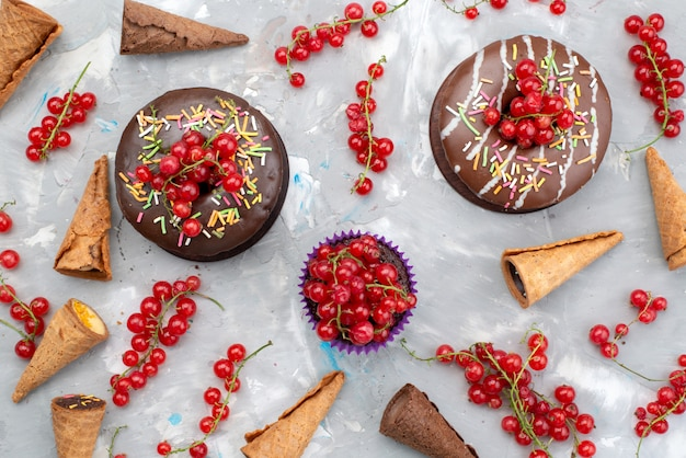 Una vista dall'alto torte al cioccolato con ciambelle progettate con frutta e corna sullo sfondo bianco torta biscotto ciambella zucchero
