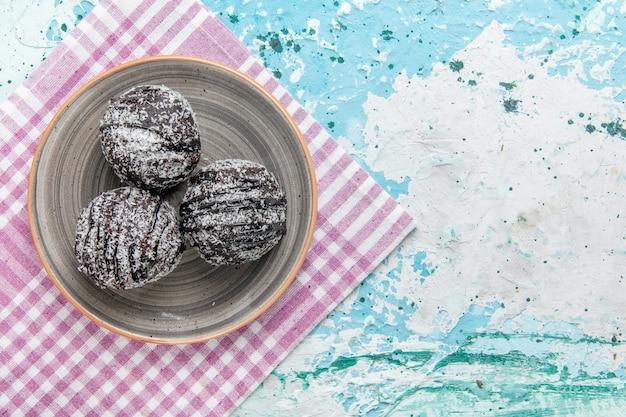 水色の背景のケーキチョコレートビスケット砂糖甘い色の上のアイシングと砂糖粉とトップビューチョコレートケーキ