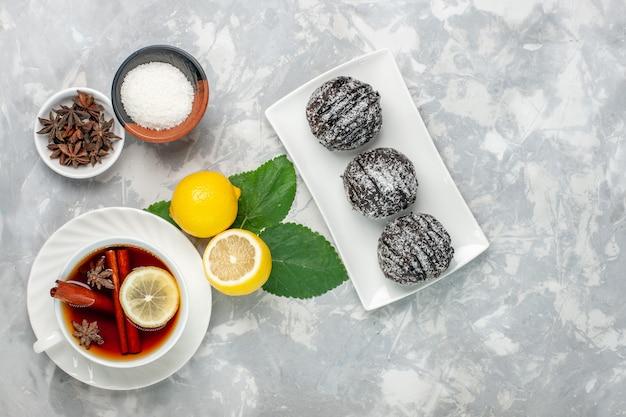 Torte al cioccolato vista dall'alto con limone e tazza di tè sulla superficie bianca