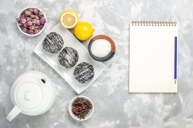 白い表面にレモンとトップビューのチョコレートケーキ