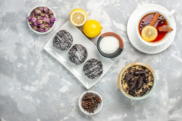Top view chocolate cakes with lemon and tea on white surface