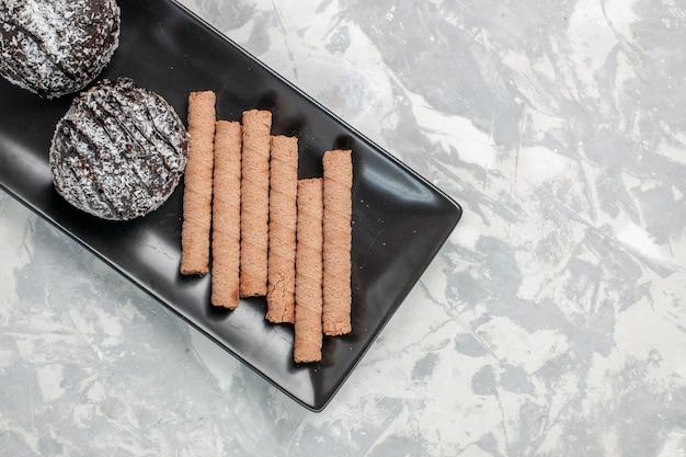 Вид сверху шоколадные торты со сладким трубочным печеньем внутри черной тарелки на белой поверхности