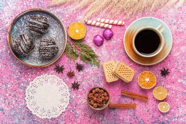Torte al cioccolato vista dall'alto con cialde e tazza di tè sul rosa