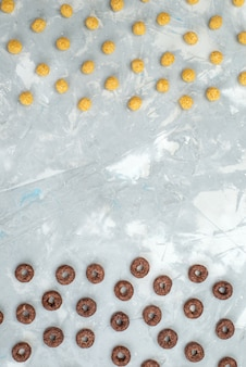 Top view chocolate cereals lined along with yellow cereals on grey