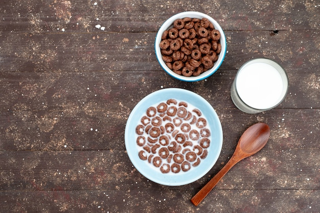 파란색 접시 안에 우유와 갈색 숟가락과 함께 상위 뷰 초콜릿 곡물