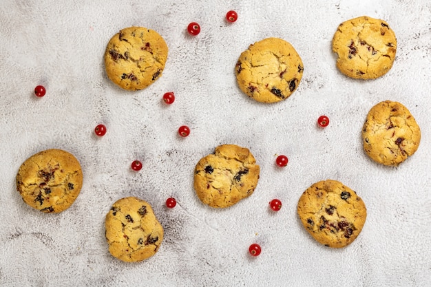 Top view of chocolate chip cookies and cranberries on a concrete surface