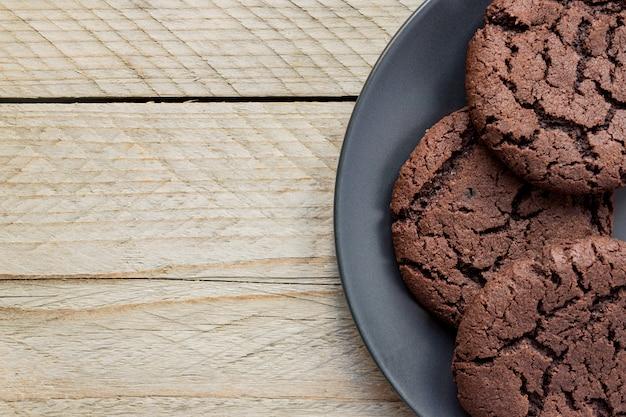 平面図、黒いプレートにチョコレートチップクッキー。木製の背景。上から。コピースペース