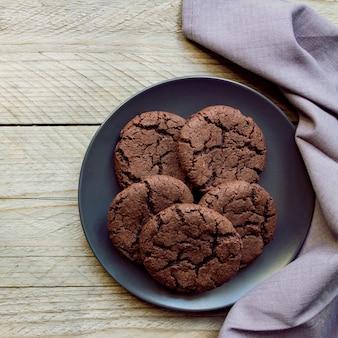 平面図、黒いプレートにチョコレートチップクッキー。木製の背景。上から。