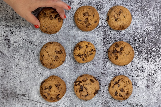 Top view of chocolate chip cookies on a textured surface with a woman taking one cookie