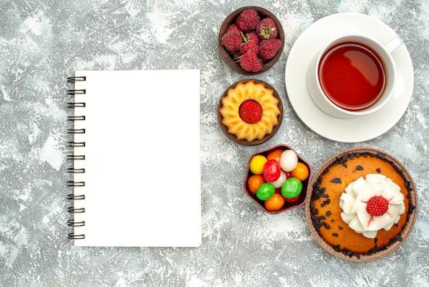 上面図白い背景の上のお茶とキャンディーとチョコレートチップケーキ甘いパイクッキービスケットケーキ砂糖