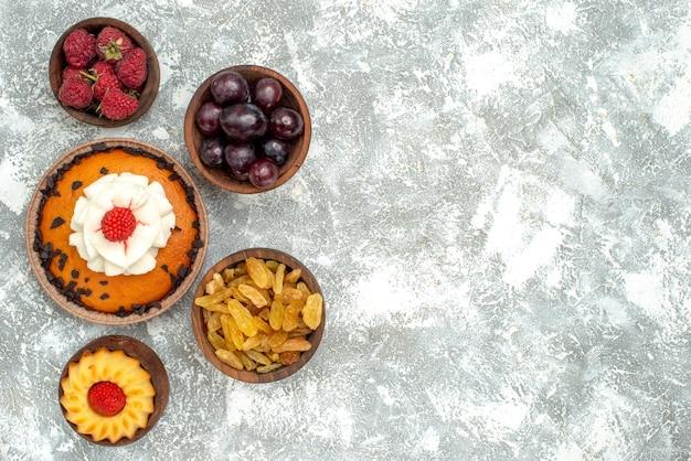白い背景の上のレーズンとフルーツのトップビューチョコレートチップケーキパイクッキービスケット甘いケーキ