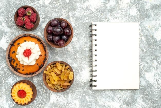 上面図白い背景の上のレーズンとフルーツとチョコレートチップケーキ甘いパイクッキービスケットケーキ砂糖