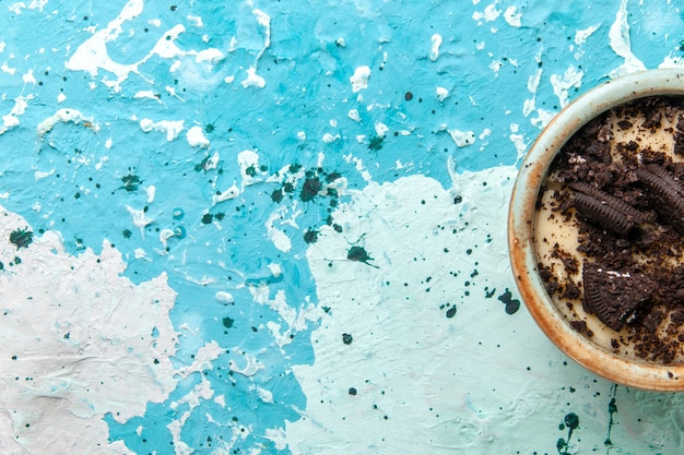 上面図チョコレートクッキーデザート、クリーム色、青い背景のプレートの内側にクッキーケーキデザート砂糖甘い色