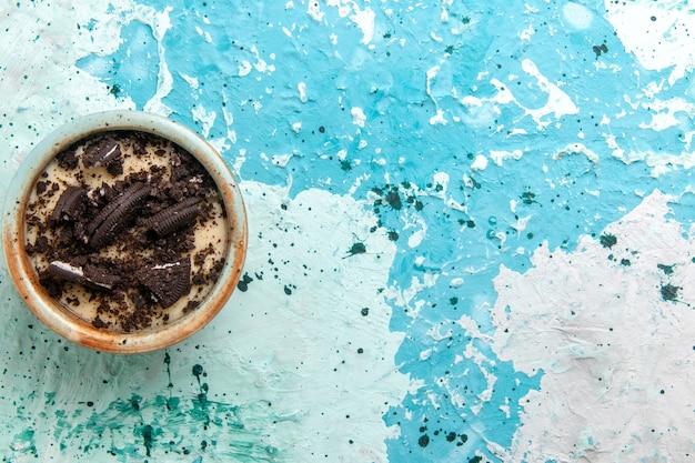 青い背景の上のプレートの中にクリームとクッキーが付いている上面図チョコレートクッキーデザートケーキデザート砂糖甘い写真