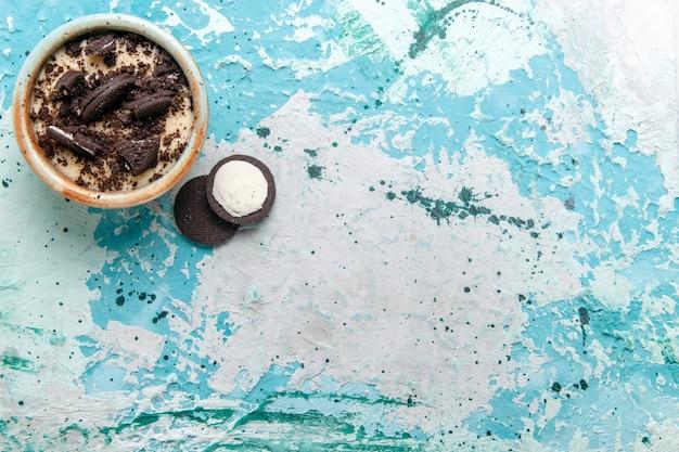 Vista superiore del biscotto al cioccolato dessert con crema e biscotti all'interno della piastra su sfondo azzurro torta da dessert zucchero dolce foto a colori