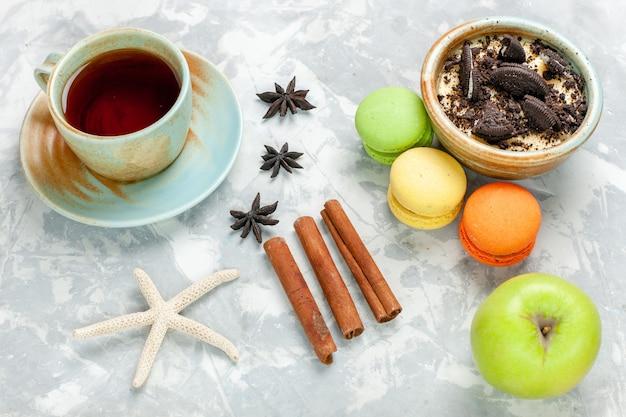 Вид сверху шоколадное печенье, десерт с французскими макаронами и чаем на светло-белом настольном печенье, сладкая выпечка, сахарный пирог, печенье