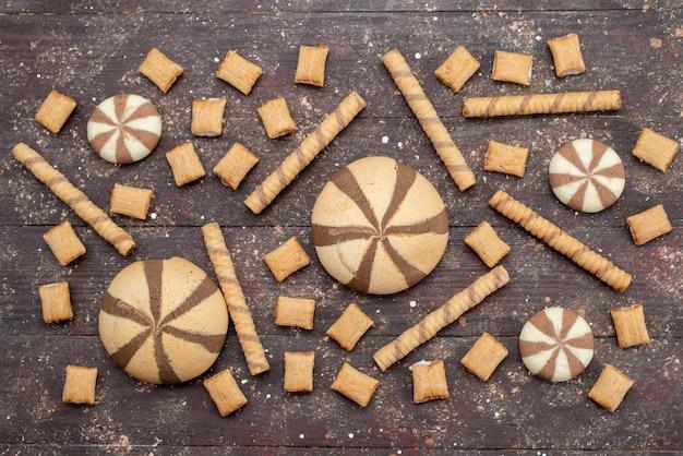 Вид сверху шоколадное печенье вкусное и сладкое на деревянном столе хрустящий сахар сладкое фото