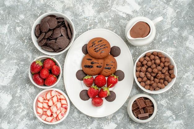 상위 뷰 초콜릿 쿠키 딸기와 흰색 타원형 접시에 둥근 초콜릿과 사탕 딸기 초콜릿 시리얼과 카카오 그릇 회색 흰색 바닥에