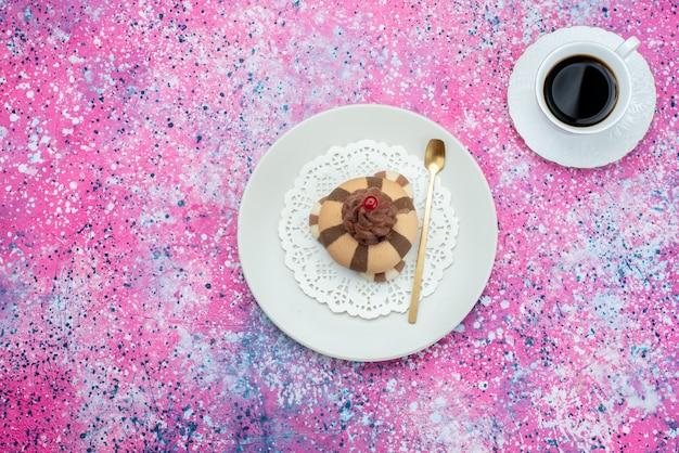 紫色の背景のクッキービスケット甘いコーヒーのカップと上面チョコレートクッキー