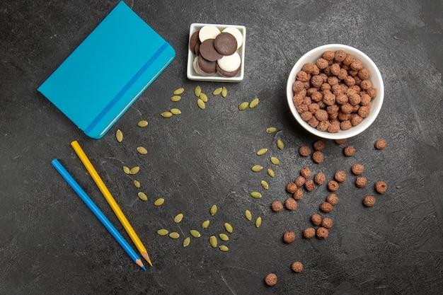 暗い背景色のクッキービスケットにフレークと鉛筆でトップビューチョコレートクッキー