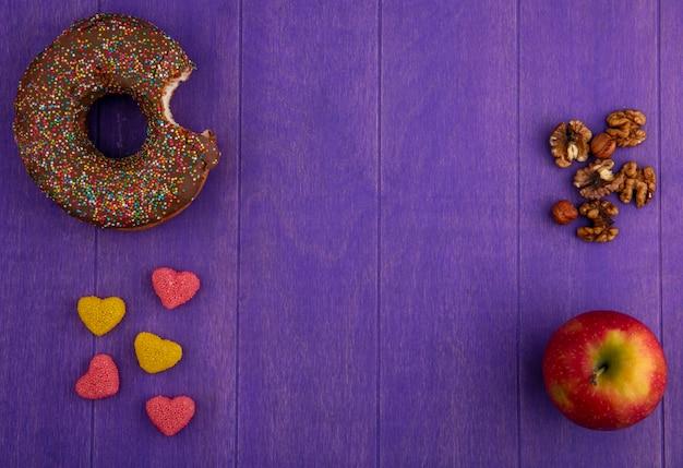 Vista dall'alto di ciambella al cioccolato con mele, noci e marmellata su una superficie viola brillante