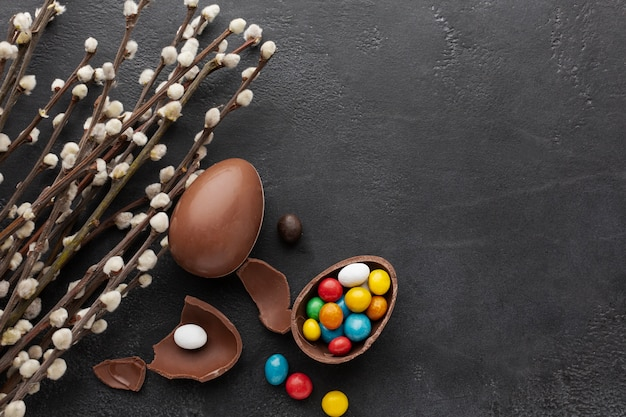 Top view of chocolate easter egg with colorful candy and flowers