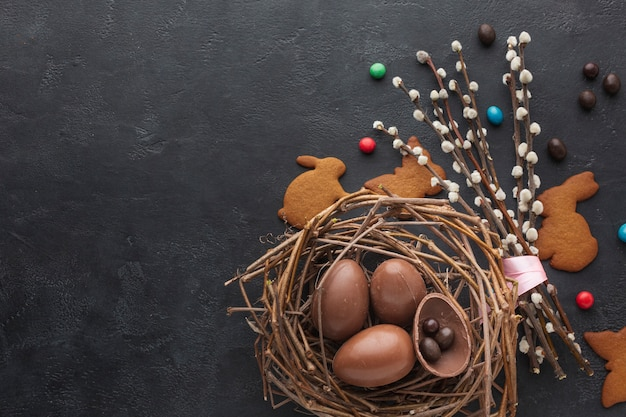 Top view of chocolate easter eggs in nest with candy and copy space