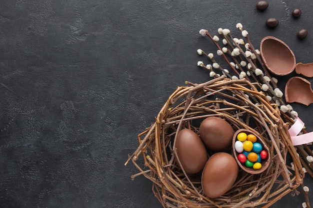 Top view of chocolate easter eggs in nest with candy and flowers
