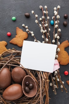 Top view of chocolate easter eggs in nest with cookies and piece of paper on top