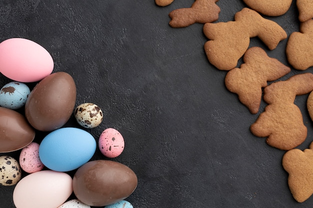 Top view of chocolate easter eggs with bunny shaped cookies